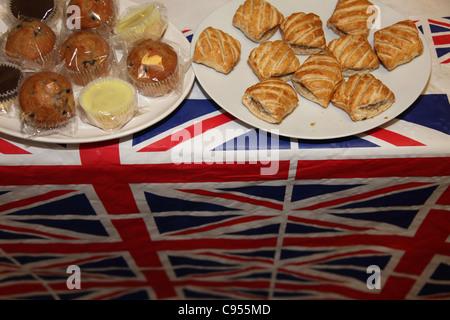 Wurstbrötchen und Cupcakes auf einer Platte auf einem Tisch mit einem Union Jack-Flagge in einem Club Royal British Legion.