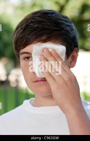 Verletzungen am Auge. Junge mit einem sterilen Verband über seine verletzten Auges. - Stockfoto