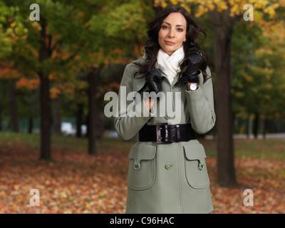 Schöne lächelnde junge Frau trägt einen grünen Mantel, ein Spaziergang durch einen Park im Herbst