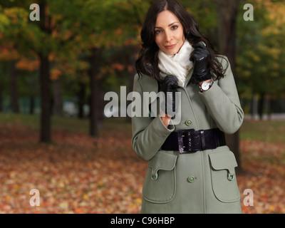 Wunderschöne lächelnde Frau trägt einen grünen Mantel, ein Spaziergang durch einen Park im Herbst