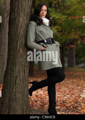 Modisch gekleidet für die Herbstsaison, schöne lächelnde junge Frau trägt einen grünen Mantel, lehnte sich gegen einen Ahornbaum im park
