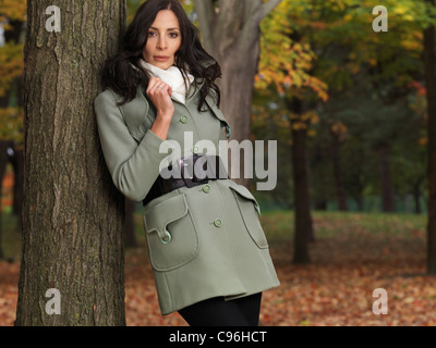Modisch gekleidet für die Herbstsaison, schöne junge Frau in einem grünen Mantel, lehnte sich gegen einen Baum in einem Park.