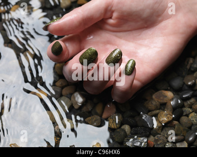 Nahaufnahme von Frau Hand mit grünen Phantasie Nagellack im Wasser liegend - Stockfoto