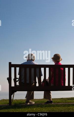 Ein älteres Ehepaar sitzen auf einer Meer-Bank, Blick auf das Meer in Southwold, Suffolk, England, Großbritannien, - Stockfoto