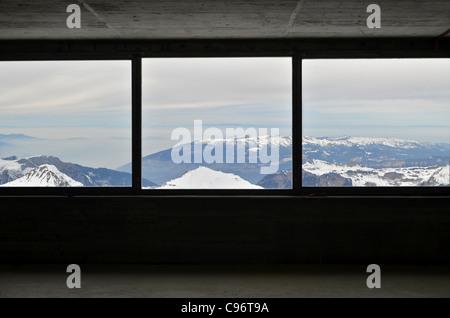 Die Jungfraubahn-Zug hält an einer Station mit einem Fenster in der Nordwand des Eigers für Besucher um zu fotografieren. - Stockfoto