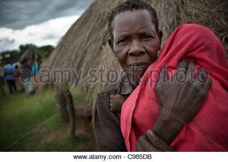 Ältere Frau mit einem Baby in einem roten Tuch gewickelt - Stockfoto