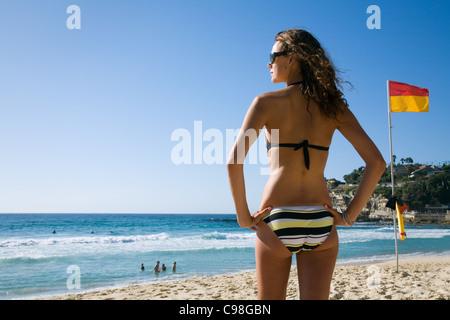Frau im Bikini stehen neben roten und gelben Surf Lifesaving Flagge am Strand. Sydney, New South Wales, Australien - Stockfoto