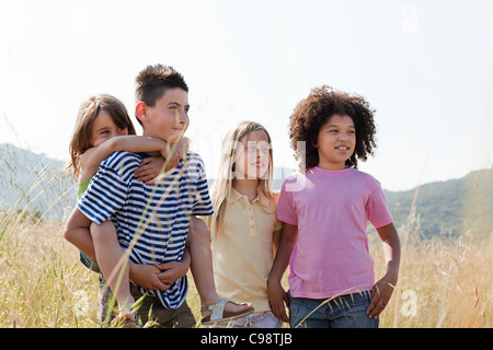 Vier Freunde im Feld, jüngste Mädchen, das Schweinchen zurück - Stockfoto