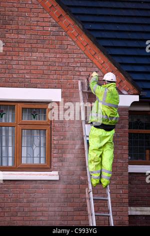 Männer auf Leitern_Polystyrol Raupe Haus Wand Isolierung, Arbeiter in Sicherheit Kabelbaum installieren Schaum Isolierung - Stockfoto