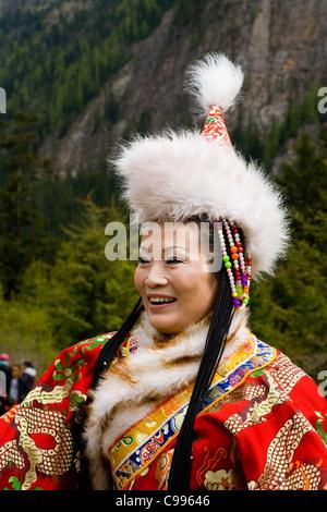 Chinesische Frauen Tourist in traditionelle tibetische Tracht / Kleid, mit Pelzmütze & langen Ärmeln. Jiuzhaigou - Stockfoto