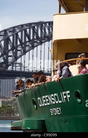Passagiere an Bord der Manly mit der Fähre am Circuar Quay, mit der Harbour Bridge im Hintergrund. Sydney, New South - Stockfoto