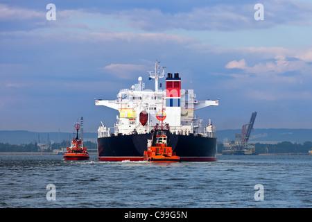 Manöver auf See an einem bewölkten Tag - Begleitung Tanker von Schleppern. - Stockfoto
