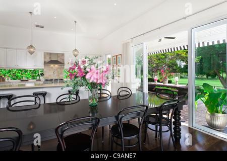 Stilvolle offene Küche mit Geräten aus rostfreiem Stahl und Essbereich mit Blick auf Pool und Golfplatz - Stockfoto