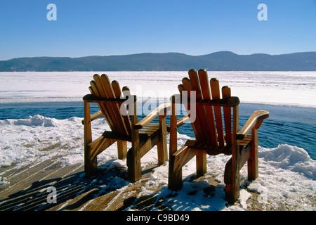 Zwei Adirondack Stühle auf einem Deck im Winter, Lake George, New York - Stockfoto