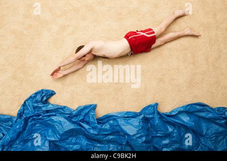 Deutschland, junger Mann springt im Wasser am Strand - Stockfoto