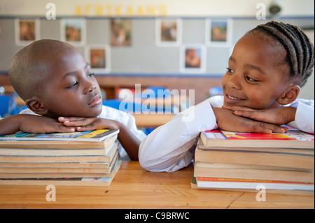 Jungen und Mädchen stützte sich auf Bücher am Schreibtisch im Klassenzimmer, Johannesburg, Provinz Gauteng, Südafrika - Stockfoto