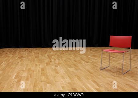 Ein Regiestuhl auf einer Bühne mit einem schwarzen Vorhang im Hintergrund - Stockfoto