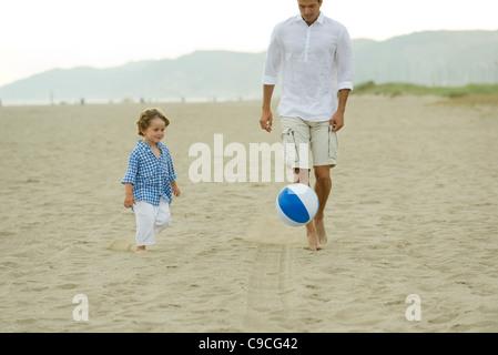 Vater und Sohn spielen mit Ball am Strand - Stockfoto