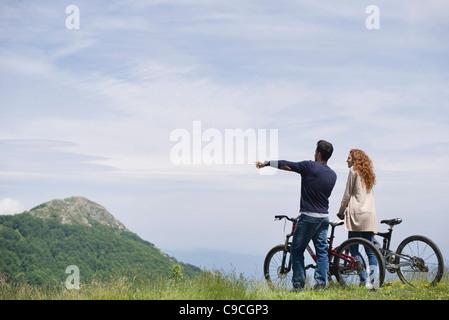 Paar stehen Mountain bikes genießen malerischen Blick auf die Berge - Stockfoto