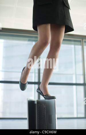 Frau stehend auf Laptop-Computer, niedrige Abschnitt - Stockfoto