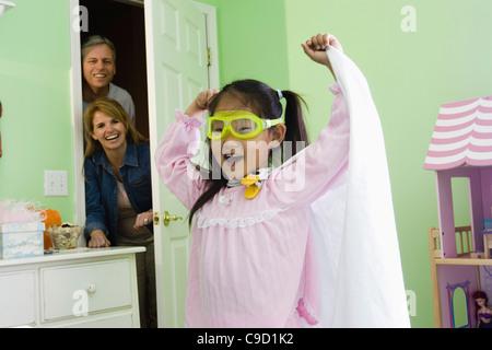 Junge Asiatin in Superhelden-Kostüm mit Eltern beobachten - Stockfoto