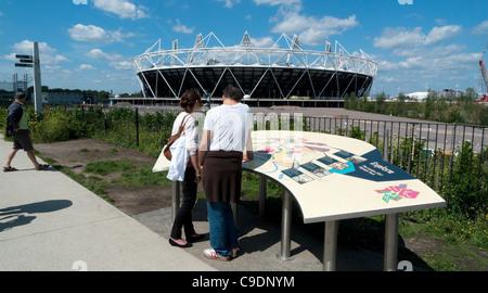 Ein paar studieren eine Informationstafel 2012 Olympic Park und Blick auf das Stadion aus der Sicht Tube Greenway - Stockfoto