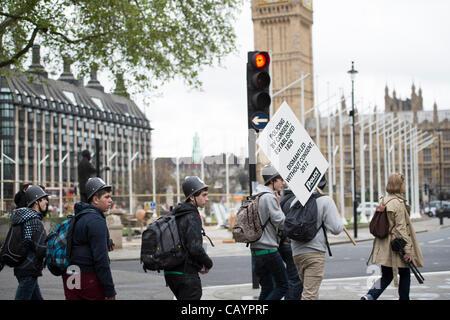 10. Mai 2012 Zentrum von London. Studenten aus Kunststoff Polizei Helmen und tragen eine ausrangierte Plakat und - Stockfoto