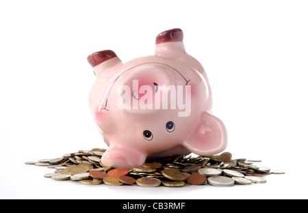 Sparschweine schwelgen in Münzen auf weißem Hintergrund - Stockfoto
