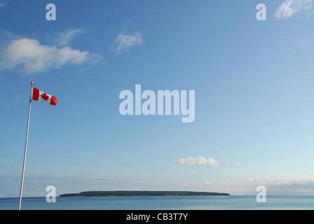 Kanadische Flagge und Griffith Insel von Big Bay Kiesstrand der Georgian Bay in Ontario, Kanada gesehen - Stockfoto