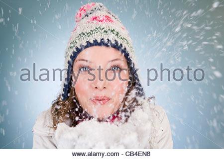 Eine junge Frau bläst eine Handvoll Schneeflocken - Stockfoto