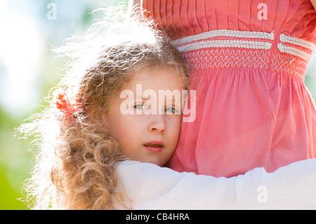 schöne kleine Tochter umarmt ihre Mutter und schaut in die Kamera. Natur-Hintergrund. - Stockfoto