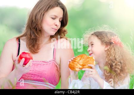 Schöne und glückliche junge Mutter mit Picknick mit ihrer kleinen Tochter, beide Lächeln, Sommerpark im Hintergrund - Stockfoto
