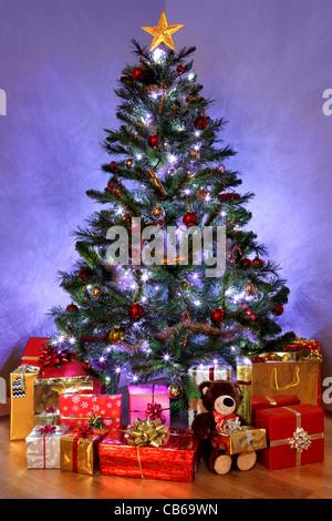 Foto von einem Weihnachtsbaum mit Dekorationen und Lichterketten umgeben von präsentiert auf einem Holzfußboden - Stockfoto