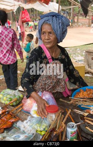 Alte Frau in einem blauen Krama kochen Fleisch Kebab bei einem Dorffest, kambodschanischen Neujahr (Chaul Chnam - Stockfoto