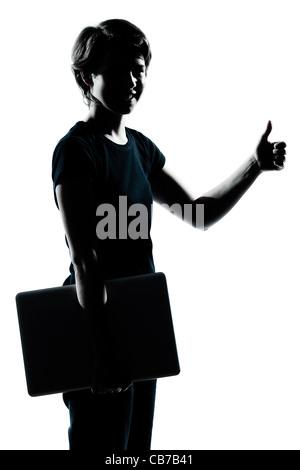 eine kaukasische junger Teenager Silhouette junge Mädchen halten tragen Laptop Computer Daumen Porträt im Studio - Stockfoto