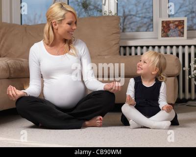Glückliche schwangere Mutter und ihre kleine Tochter gemeinsam Spaß haben beim Yoga zu Hause - Stockfoto