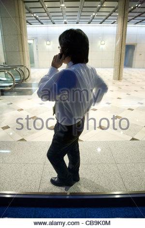 junger Geschäftsmann Fenster gelehnt, während des Gesprächs auf sein Handy - Stockfoto