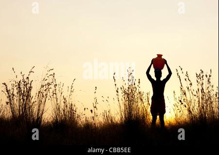 indischer Mann bei Sonnenuntergang mit einem Wassertopf auf diesem Kopf in der indischen Landschaft wandern. Silhouette - Stockfoto