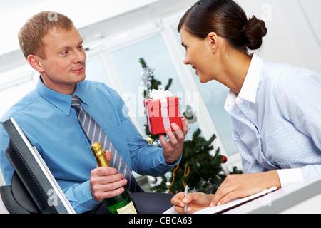 Porträt des jungen Geschäftsmann mit Flasche Champagner, geben seinem Kollegen anwesend - Stockfoto