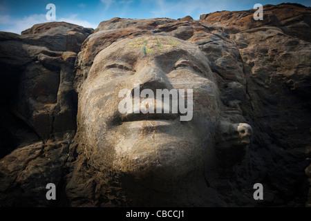 Das Gesicht des Shiva geschnitzt in Felsen auf kleinen Vagator Beach, North Goa, Indien