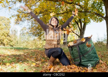 Frau spielt mit Herbstlaub im park - Stockfoto
