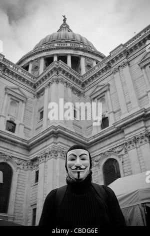 London-Demonstrant tragen einen Guy Fawkes Maske Stand vor der Kuppel der St. Pauls Cathedral, London zu besetzen. - Stockfoto