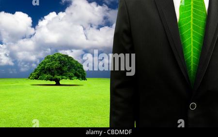 grüne Business-Konzept. Geschäftsmann mit Blatt Krawatte und alten Baum Hintergrund - Stockfoto