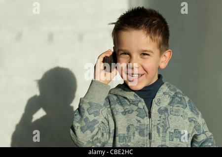 Lächelndes Kind im Gespräch mit dem Handy - Stockfoto
