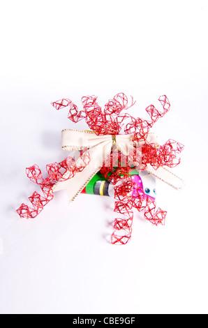 Ein wild dekoriert Weihnachtsgeschenk mit einem weißen samt Bogen und rotes Band. - Stockfoto
