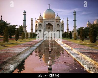 Taj Mahal bei Sonnenuntergang, Ansicht von vorne, zentriert auf den Pool mit Garten an den Seiten. - Stockfoto