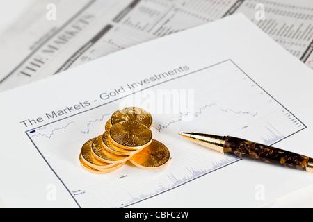 Gold Eagle 1 Unze Münzen gestapelt in Graphen des Goldes im Wirtschaftsteil der Zeitung mit Diagramme, Drop in Preise - Stockfoto