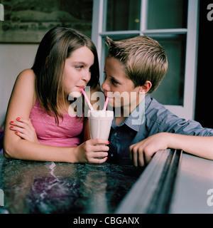 Ein junger Teenager Paar teilen einen Milchshake in einem diner - Stockfoto