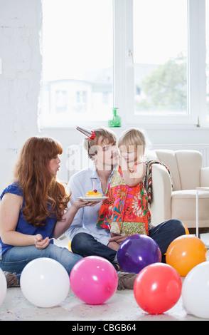 Zwei junge Eltern ihre Tochter Geburtstag mit ihr feiern - Stockfoto