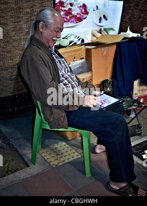Ein älterer asiatischen Mann mit einem iPad Tablet, um Spiele zu spielen und eindeutig das Erlebnis zu genießen. - Stockfoto